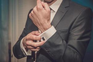 brudgummen sätter på manschettknappar foto