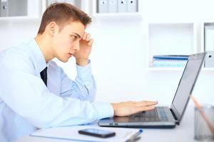 ung affärsman som arbetar på bärbar dator i office foto