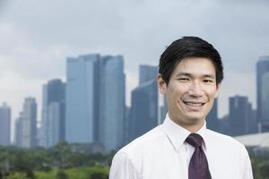 glad asiatisk affärsman framför staden. foto