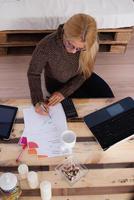inhemsk ekonomi. kvinna som kontrollerar räkningar hemma foto