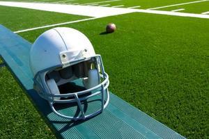 amerikansk fotbollhjälm på bänken foto
