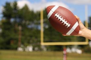 amerikansk fotboll i hand över fält med målstolpe foto