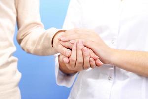 läkare håller handen på patienten, på ljus bakgrund