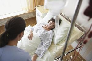 sjuksköterska med patient på sjukhusrum foto