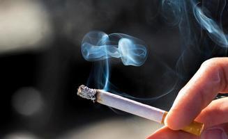håller en cigarett foto