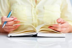 ung kvinna skriver till svart dagbok foto