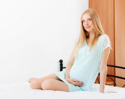 graviditet kvinna sitter i sängen hemma foto
