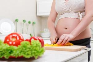 ung kvinna skär grönsaker foto