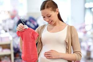glad gravid kvinna som shoppar i klädaffär foto