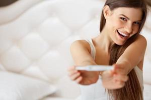 glad kvinna med graviditetstest foto