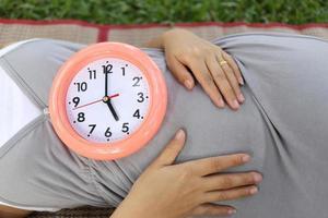 gravida kvinnor visar klockan på magen. foto
