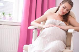 gravid kvinna i en stol foto