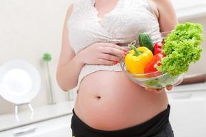 gravid kvinna med skål och grönsaker foto