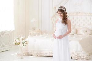 glad gravid kvinna i en ljus interiör foto