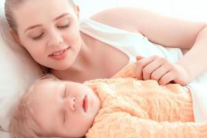 sovande barn och hans mamma foto