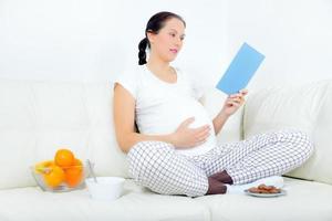 gravid kvinna vilar på soffan och läser en bok. foto