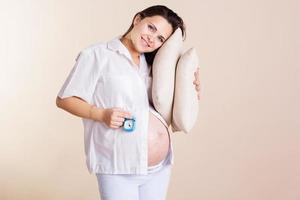 gravid kvinna i pyjamas med kudde foto