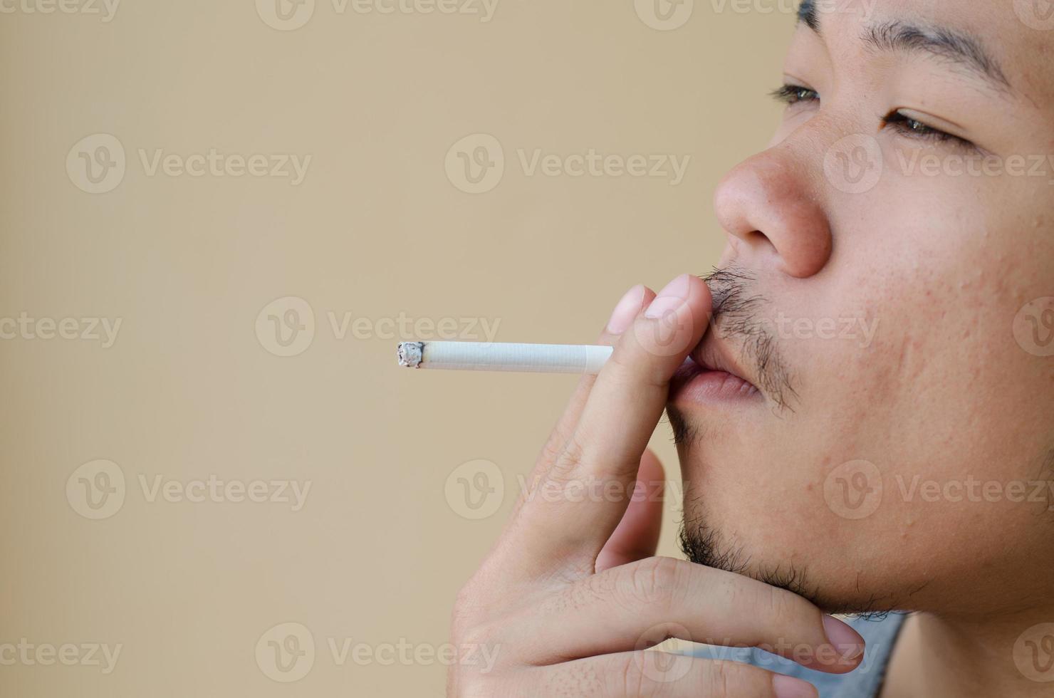 Aziatische jonge man roken sigaret foto