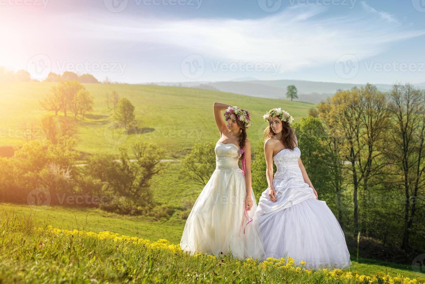 2 mooie bruid op een weide in de vroege ochtend foto