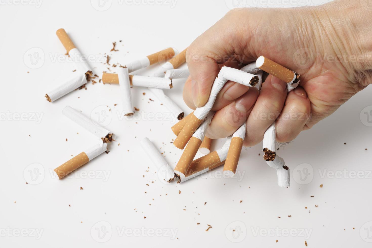 breken van sigaretten voor stoppen met roken op witte achtergrond foto