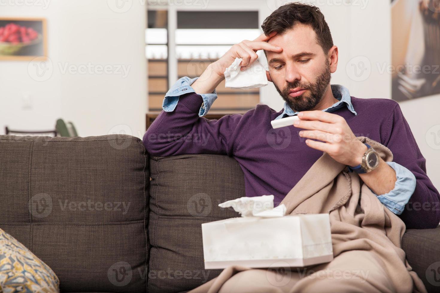 man met verkoudheid en koorts thuis foto