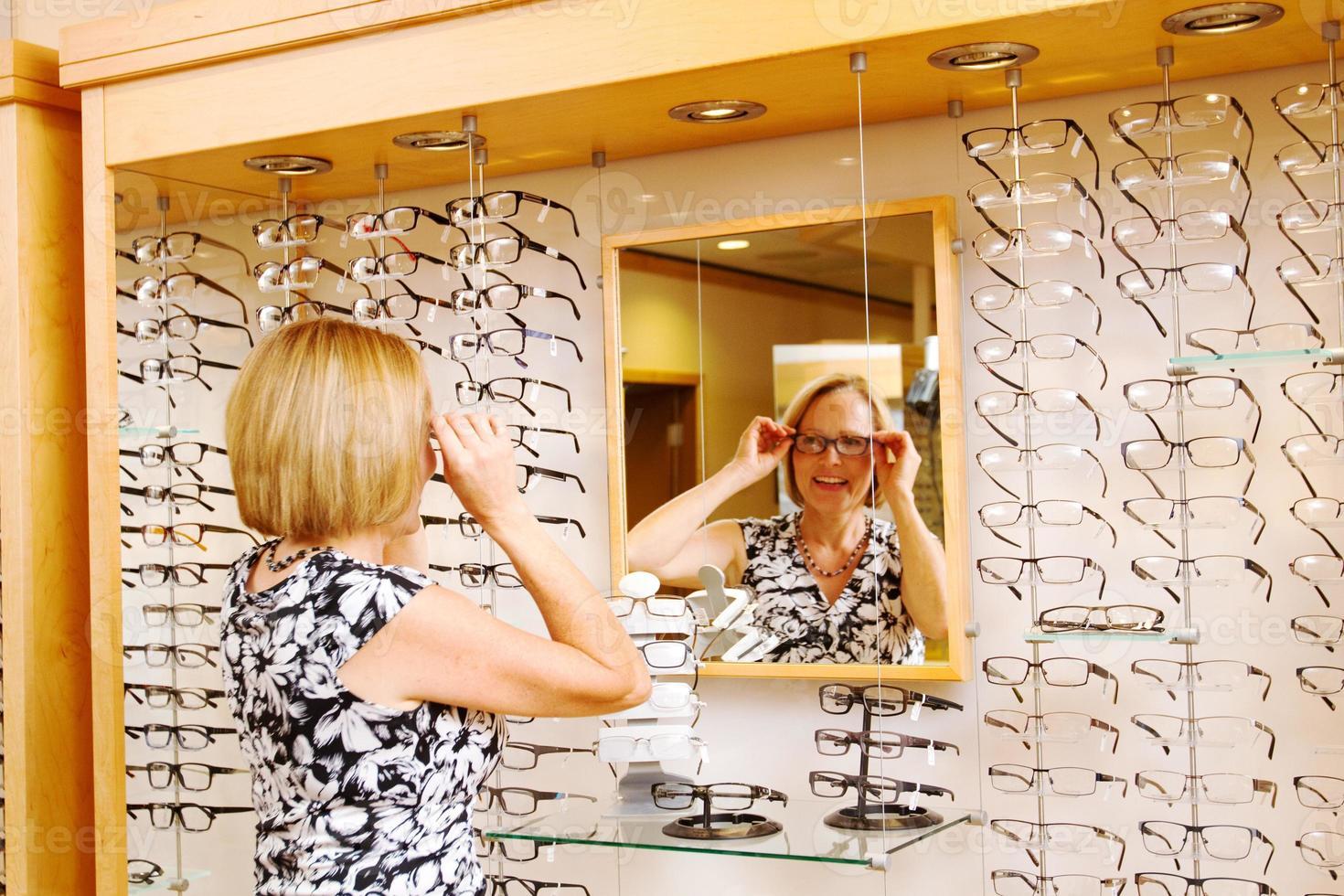 dame die een bril probeert foto
