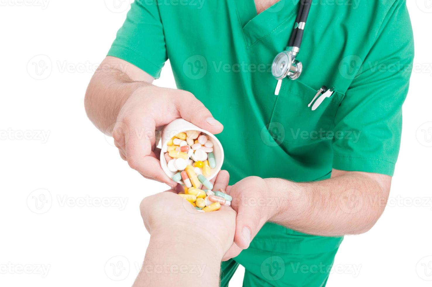 arts, dokter of apotheker pillen in de hand van de patiënt gieten foto