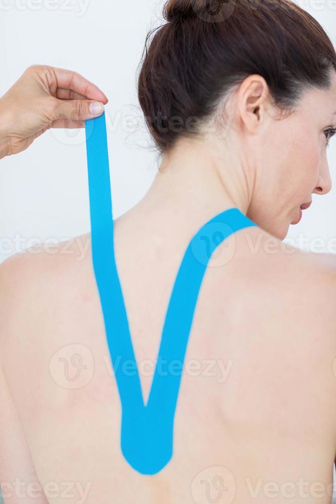 fysiotherapeut die blauwe kinesiotape op de rug van de patiënt aanbrengt foto