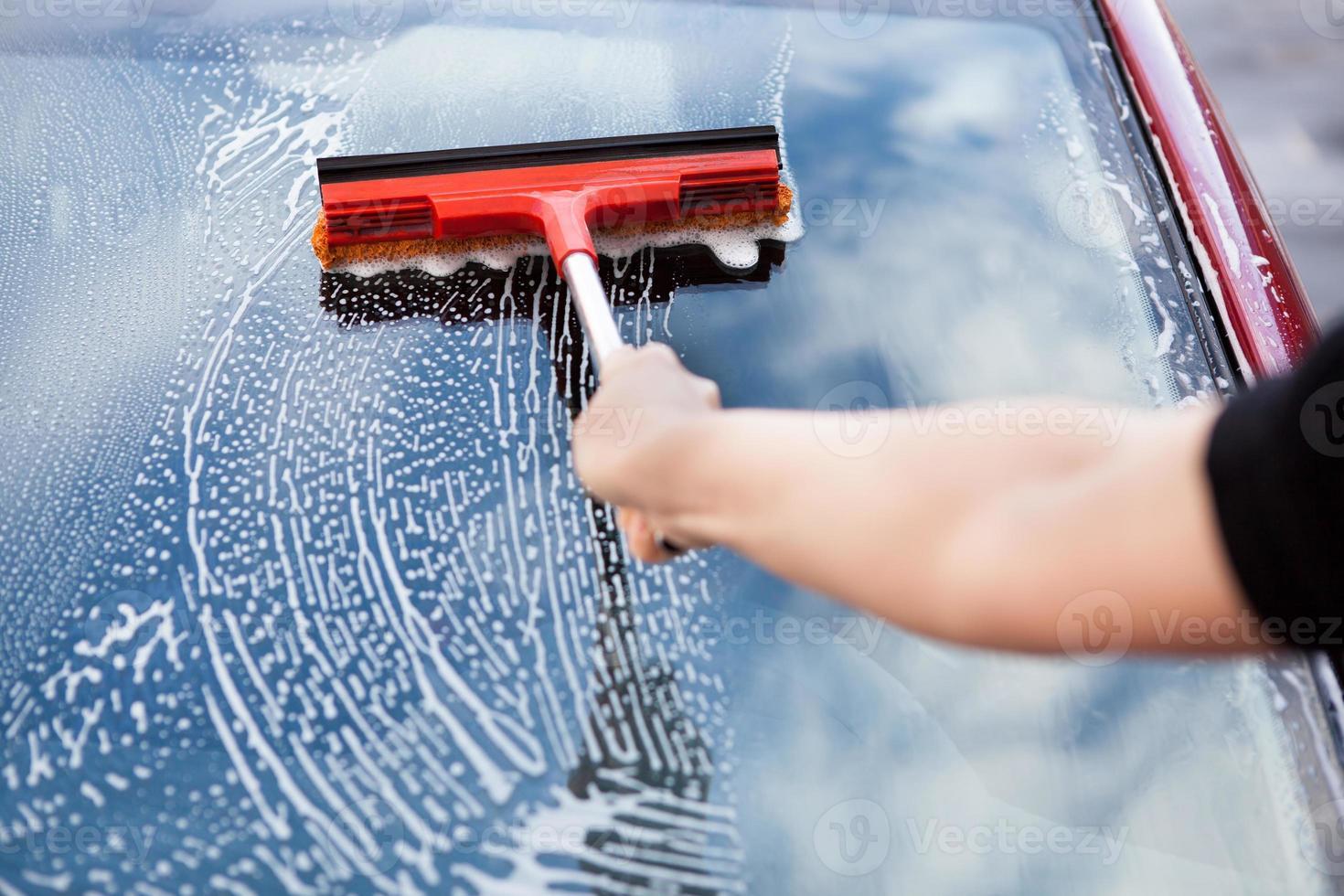 hand met mop op auto foto