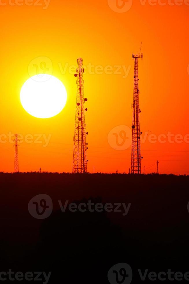 zonsondergang met tv-antennes foto