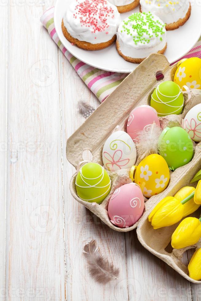 Pasen met gele tulpen, kleurrijke eieren en traditionele taarten foto