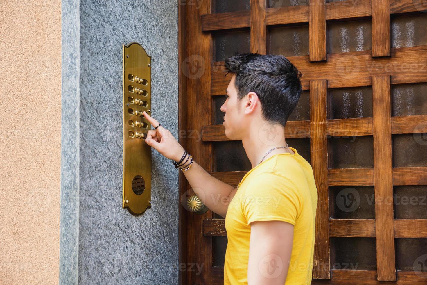 jonge man deurbel rinkelen en praten over de luidspreker foto