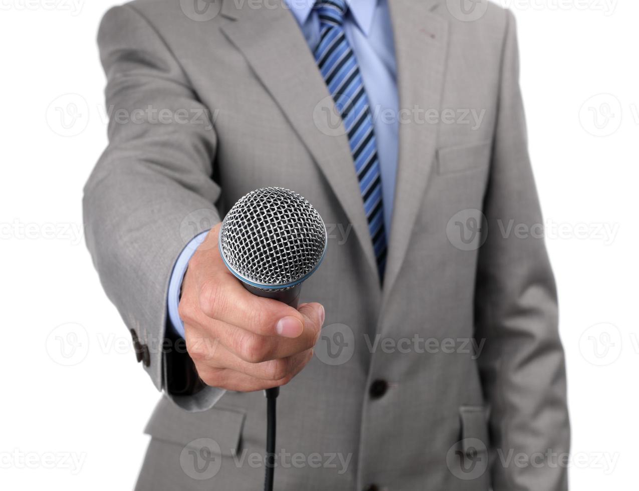 man in een pak met een microfoon naar de camera foto