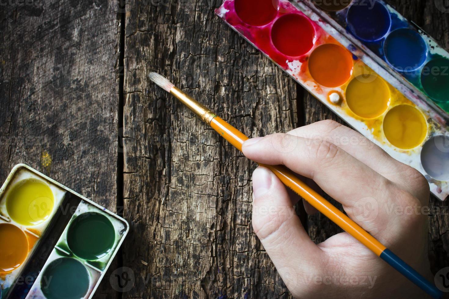 hand van de kunstenaar met een penseel om te tekenen foto