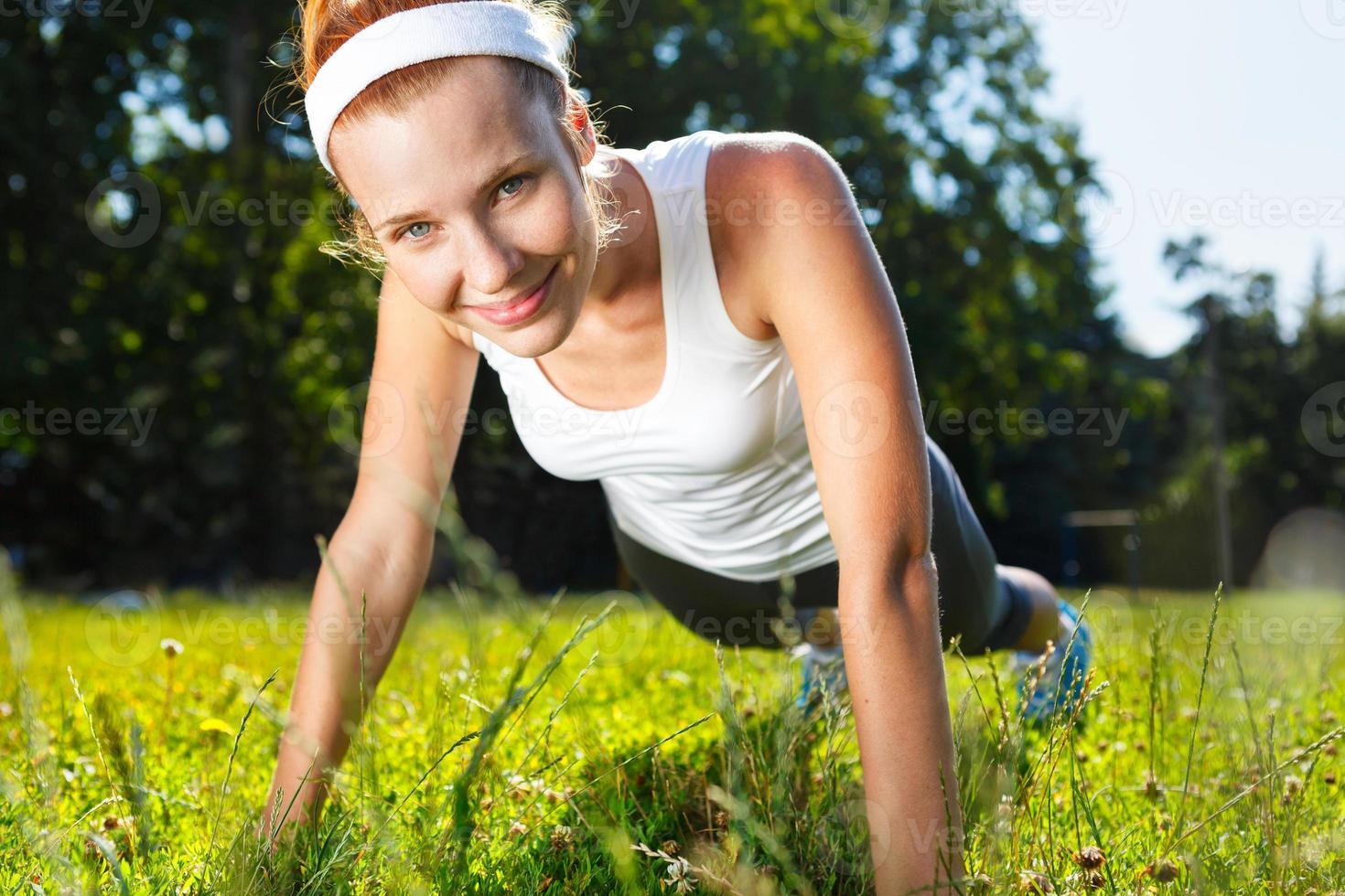 jonge vrouw doet push-ups op groen gras. foto