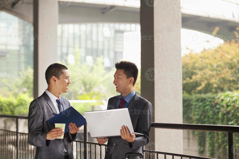 twee jonge ondernemers werken buiten, kijken elkaar aan foto