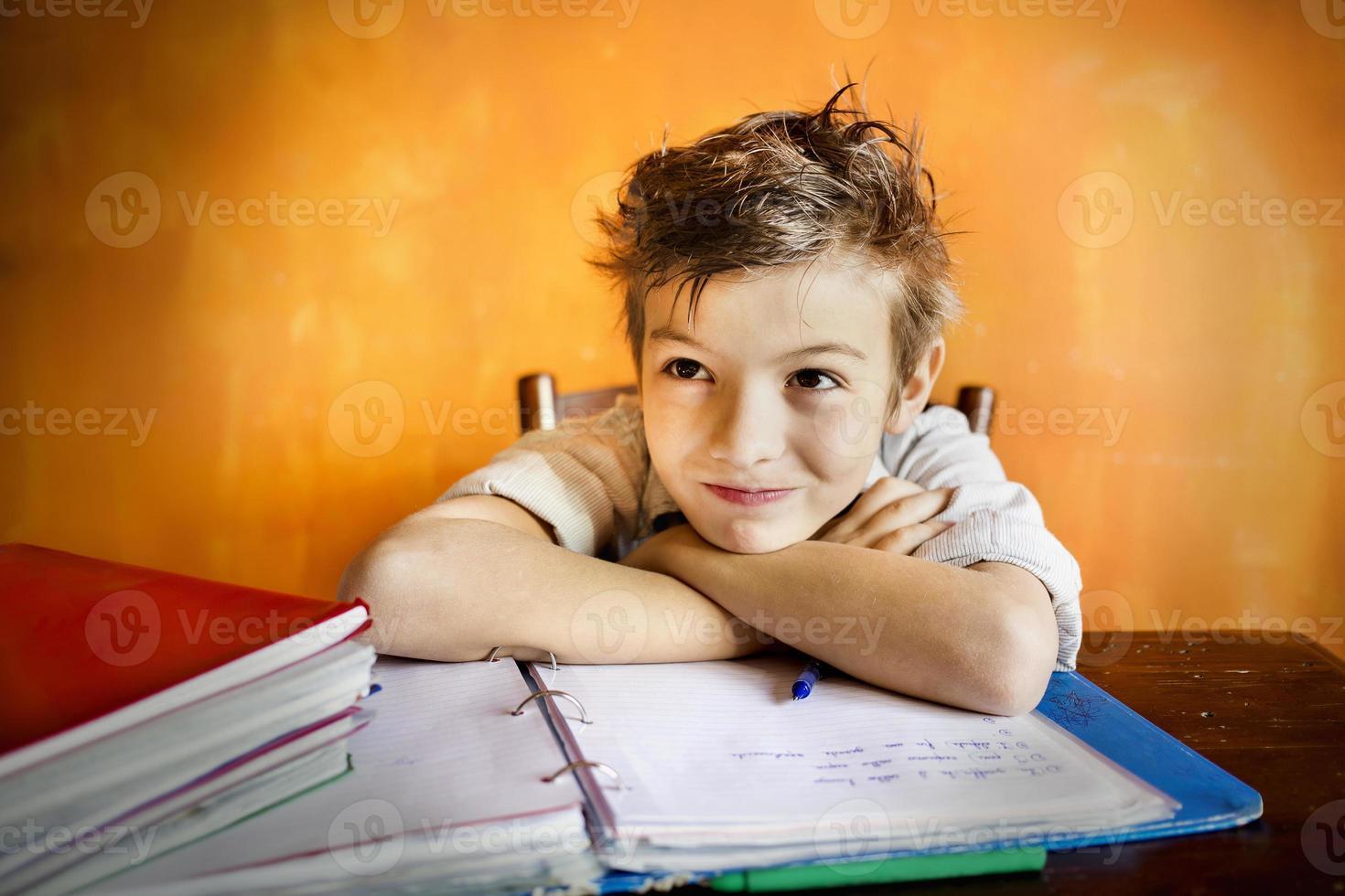 jonge jongen die zich op huiswerk concentreert foto