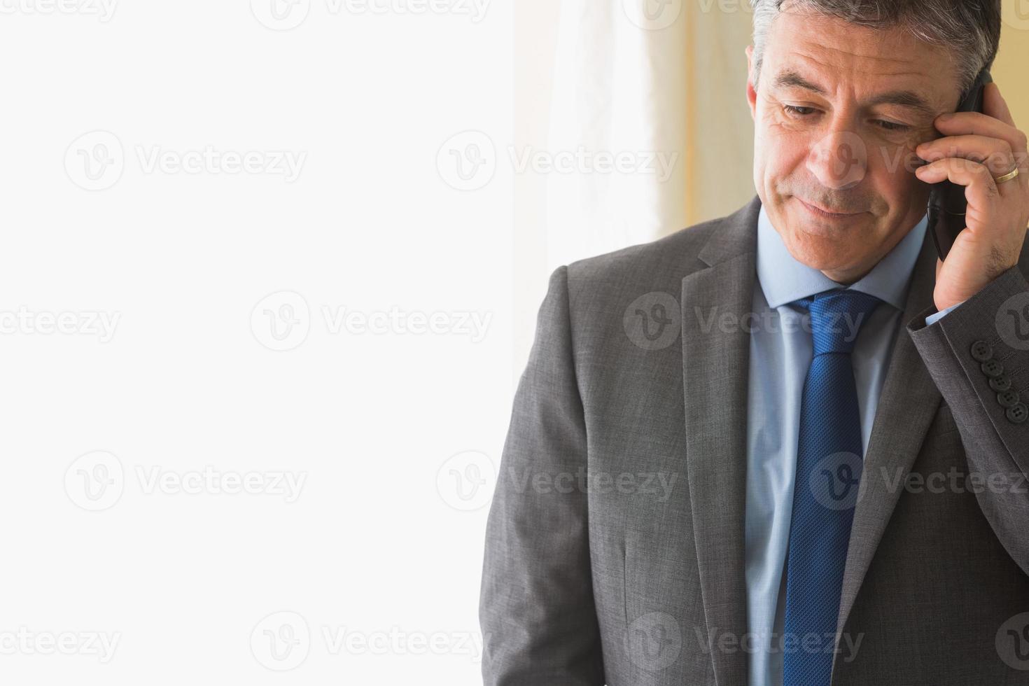 geconcentreerde man die iemand belt met zijn mobiele telefoon foto