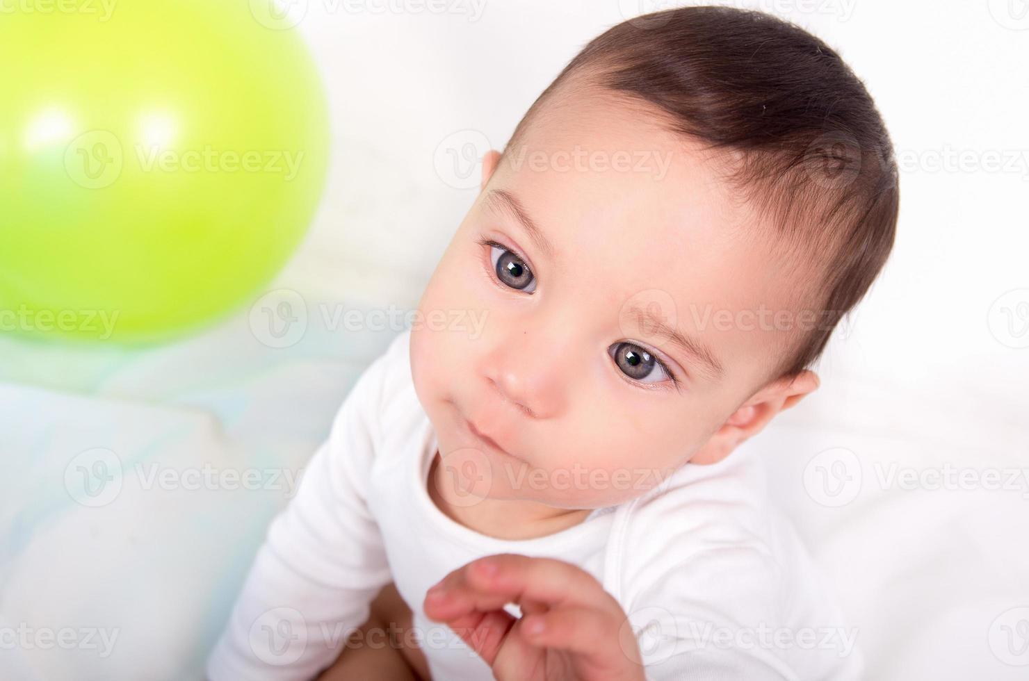 doordachte schattige babyjongen met een intens geconcentreerde look foto