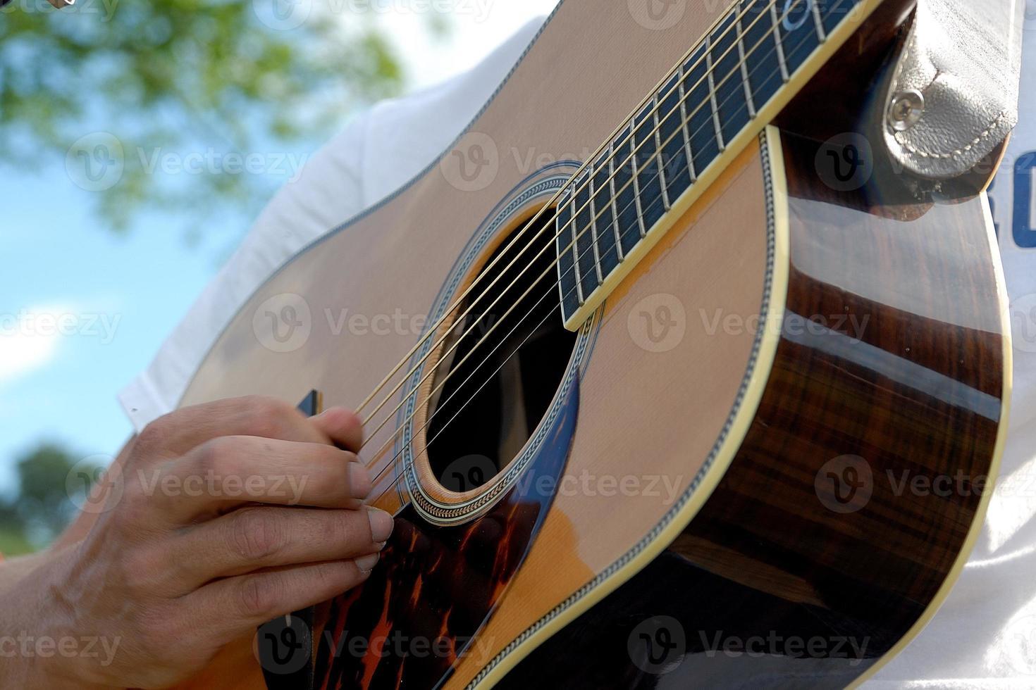 persoon die een gitaar in openlucht speelt foto