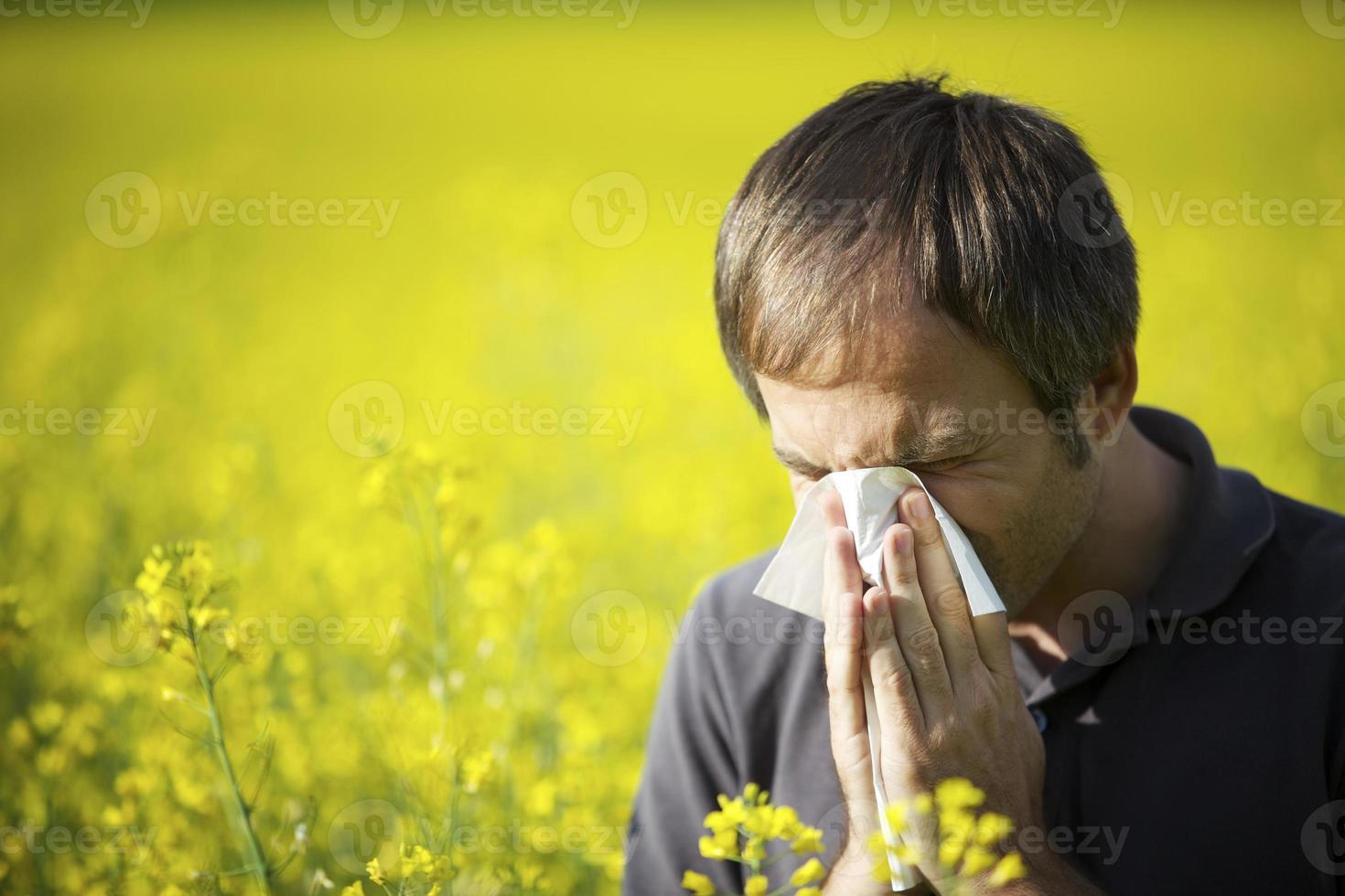 man blaast zijn neus in canola veld foto