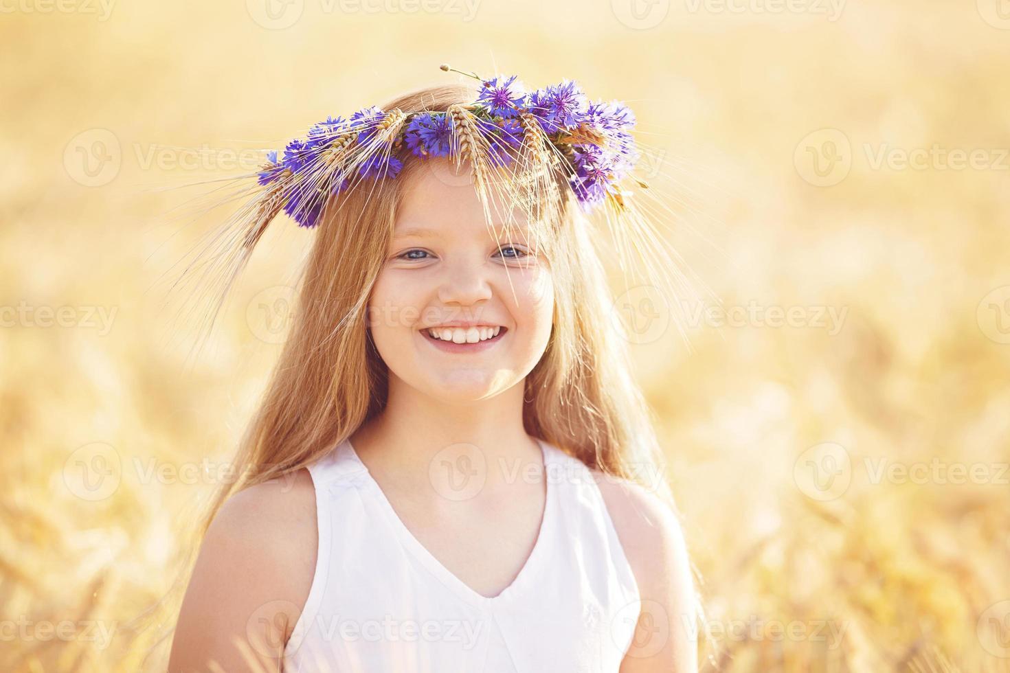 gelukkig meisje met bloemen kroon in zomer tarweveld foto