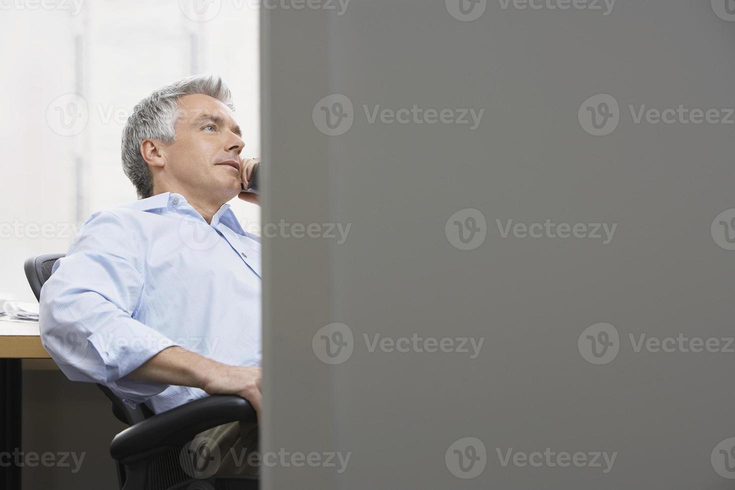 zakenman die telefoon in bureau met behulp van foto