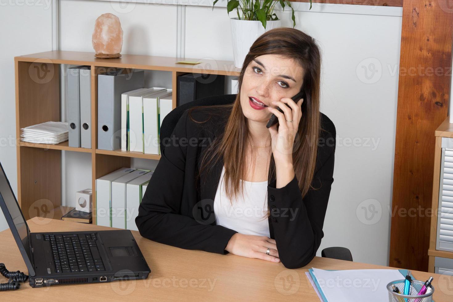 gelukkig slimme zakenvrouw aan de telefoon in heldere office foto