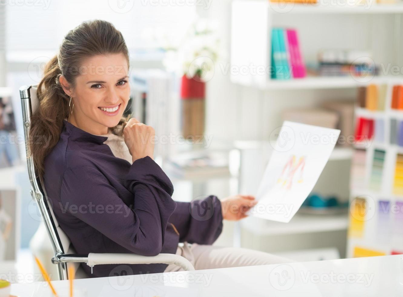 gelukkig modeontwerper met schets in kantoor foto