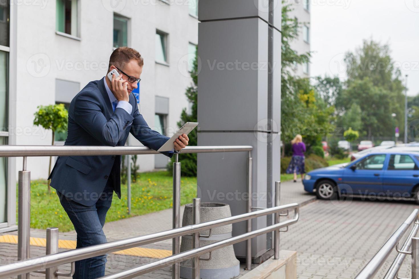 Kaukasische zakenman buiten kantoor met behulp van mobiele telefoon en tablet-pc. foto