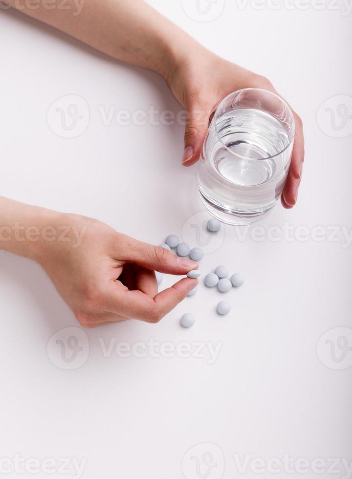 vrouwelijke handen die geneeskundepillen en glas water houden foto