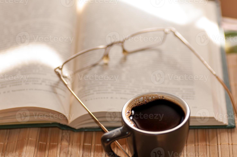 kopje koffie, staande naast een open boek foto