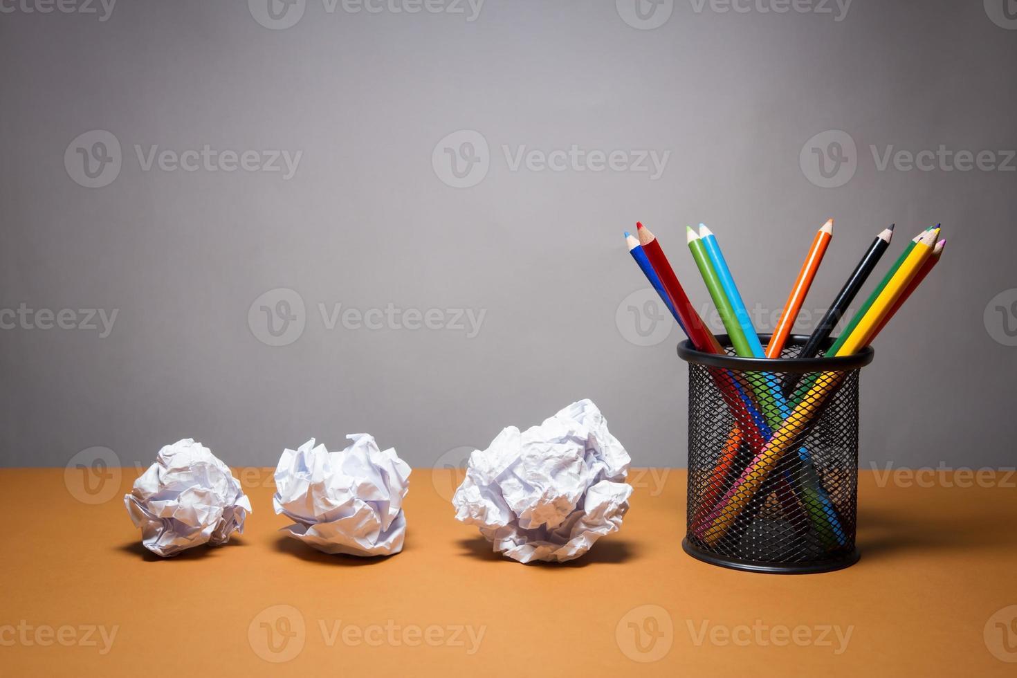 stapel kleurpotloden en verfrommeld papier. bedrijfsconcept frustraties. foto