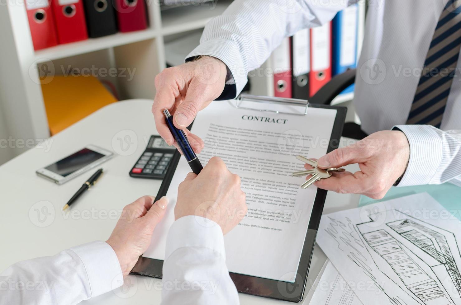 makelaar die een pen aan zijn cliënt geeft om contract te ondertekenen foto